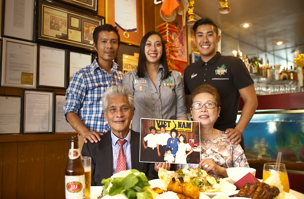 The Phan family in the Adelaide Vietnam restaurant with food on the table